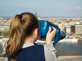 foto of binoculars  - Girl looking at coin operated binocular in Budapest Hungary - JPG