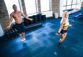pic of roping  - Fitness man and woman workout with jumping rope in crossfit gym - JPG