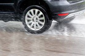 picture of wet  - car driving in the rain on a wet road - JPG