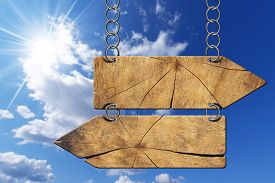picture of opposites  - Wooden directional sign with two empty arrows in opposite direction hanging with metal chain on blue sky with clouds and sun rays - JPG