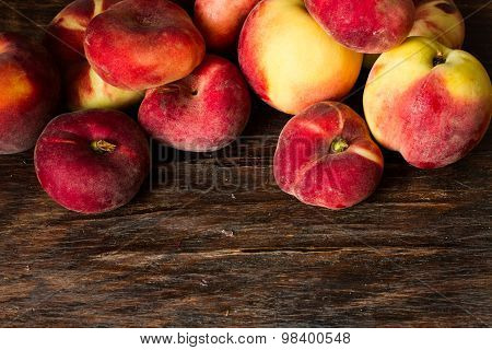 Flat Ripe Peach And The Usual Peach On A Wooden Background