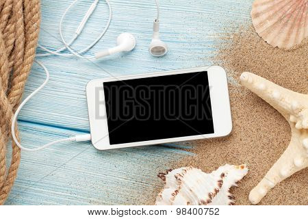 Smartphone on wood and sea sand with starfish and shells. Top view with copy space