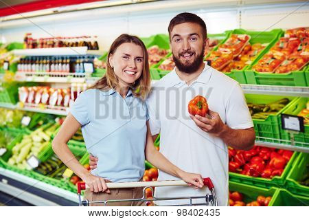 Happy couple buying vegetables in supermarket