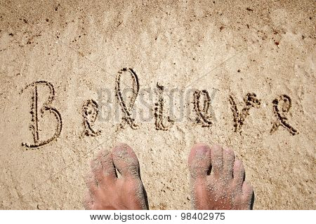 Concept or conceptual believe text handwritten in sand on a beach background with feet