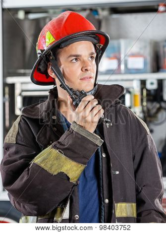 Confident male firefighter looking away while using walkie talkie at fire station