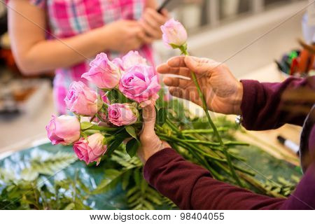 Cropped image of female worker making bouquet of roses for customer in flower shop