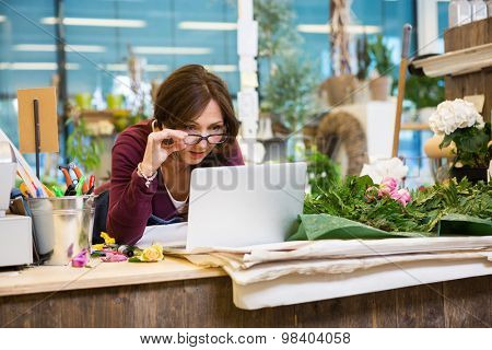 Shocked mid adult female florist holding glasses while using laptop at counter in flower shop