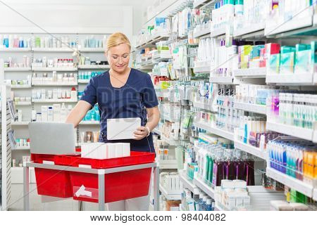 Mature female chemist updating stock in laptop at pharmacy