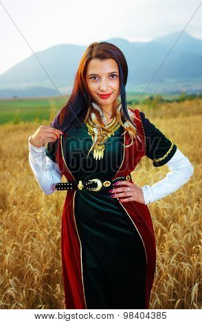 young woman with dark hair, green and red velvet historical dress and gold jewel and a subtle smile