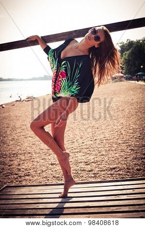young beautiful woman in bikini and summer top pose on the lake beach, full body shot