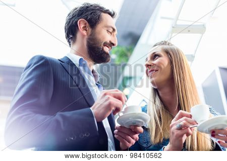 Man flirting with woman while drinking coffee