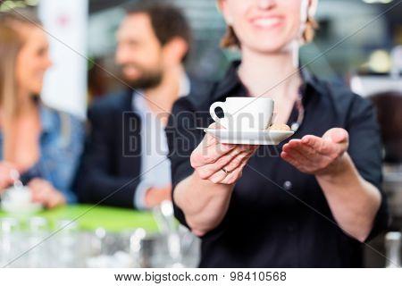 Barista presenting espresso in cafe