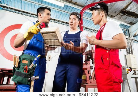 Team of Asian workers discussing product as a work team