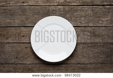 Empty plate on old wooden background. Top view