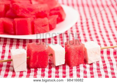 pieces of watermelon and white cheese on sticks , with watermelon plate