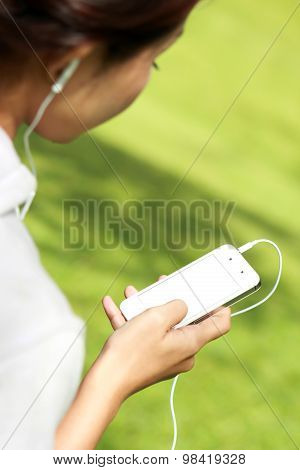 A Woman Listening A Music In Mobilephone Using Earphone