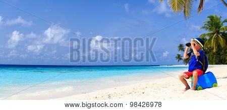 little boy travel on summer tropical beach with suitcase