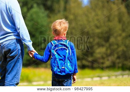 father holding hand of little son with backpack outdoors