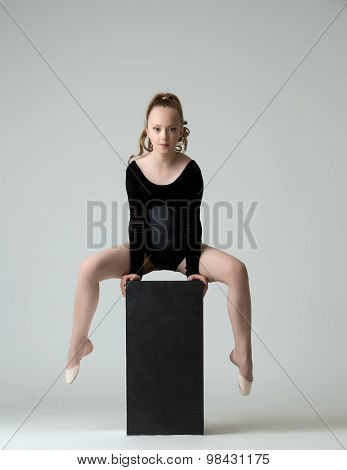 Beautiful young gymnast training on cube