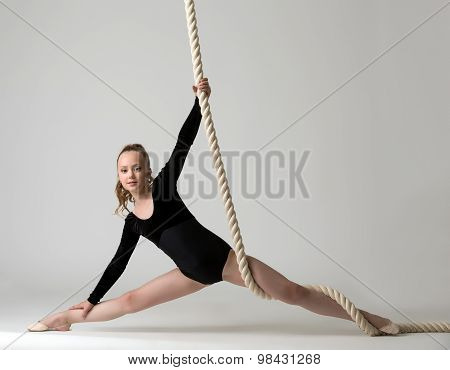 Photo of nice young gymnast training on rope