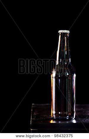 Bottles of beer and glass getting cool on black background