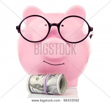 Piggy bank in glasses with dollars isolated on white