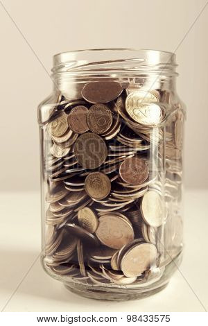 Coins in money jar on gray background