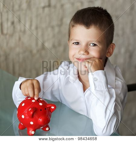 Little Boy Insert Coin Into Piggy Bank In Office
