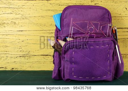 School backpack on wooden background