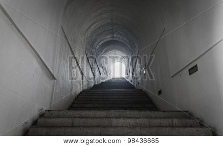 Light of the end of tunnel with ascending stairs.