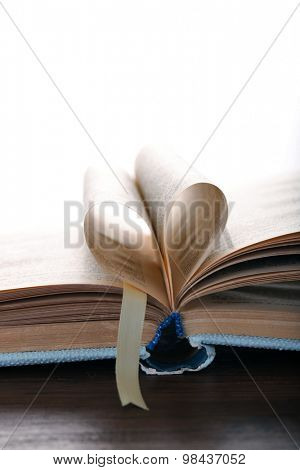 Pages of book curved into heart shape,  on white background