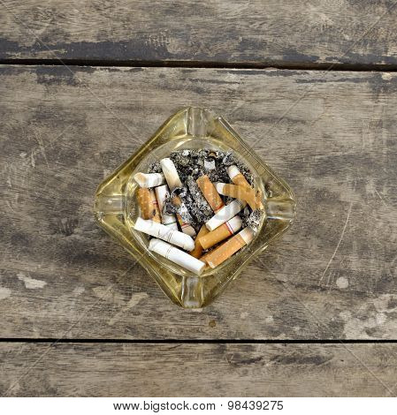 Ashtray Full Of Butt Cigarettes On Wooden Background