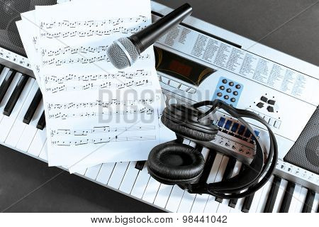 Headphones with music notes and microphone on synthesizer close up