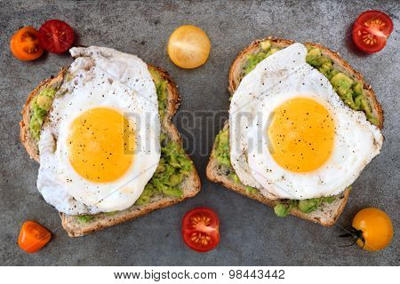 Avocado, egg toast with tomatoes on rustic baking tray