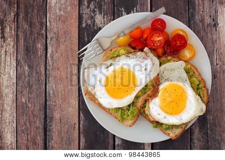 Healthy avocado, egg toasts with tomatoes on rustic wood background