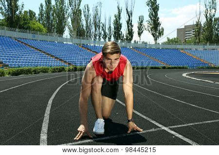 Runner in start position on stadium