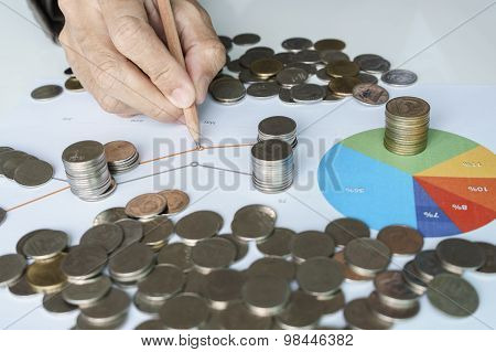 Hand Pointing To Chart And Money Coins