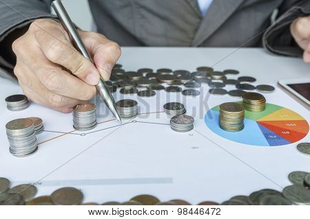 Hand Pointing To Graph And Planning Money Investment