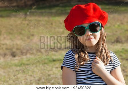 portrait of little girl with a red basque, outdoors
