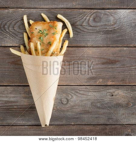 Fish and chips. Top view fried fish fillet with french fries wrapped by paper cone, on wooden background.