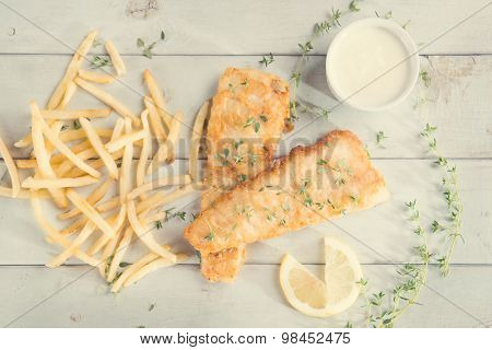 Fish and chips. Above view fried fish fillet with french fries on wooden background, vintage tone.
