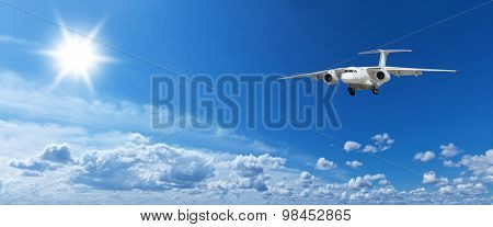 White heap clouds, airplane and bright sun in the blue sky.