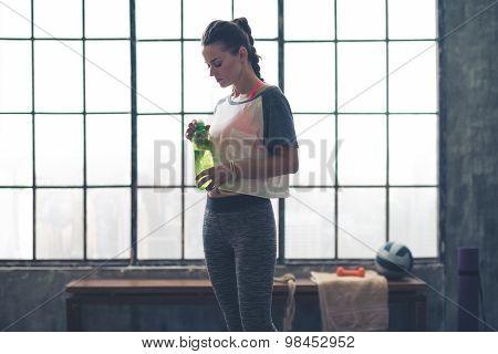 Fit Woman Standing In Profile In Loft Gym Holding Water Bottle