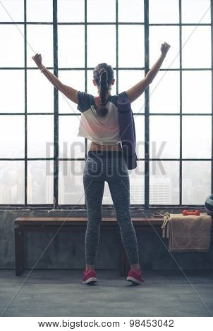 Rear View Of Woman Rejoicing In City Loft Gym