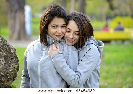 Two beautiful young women hugging outside next to a tree