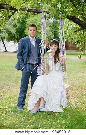 portrait of the bride and groom on a swing