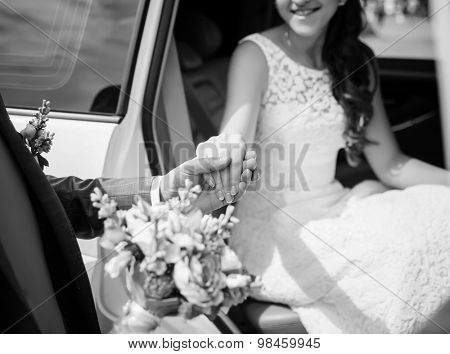 Groom helping his bride out of the wedding car. Selective focus on hands