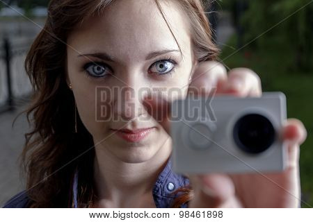 Young women with action camera in hand closeup. Peoples journalism concept.