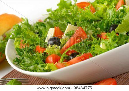 detail of fresh vegetable salad in white bowl