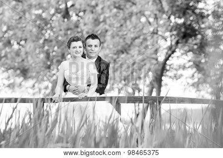 Married Couple Posing On Wooden Bridge Bw